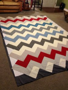 Using the strip method to make chevrons means cutting off the jagged edges after it has been pieced.  I don't like to square up my quilts until after they have been quilted, so I didn't trim up the top before pinning and quilting.  Hard part- recognizing how much will get wasted around the edges!