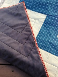Oh how I love all of the straight lines in this quilt!  Lots of careful planning to execute, but fabulous results!  (Don't ya love how the quilting looks in the minky?!? As heavy as it is to work with, it is so great to see the results, and who doesn't love some ultra softness on the back of their quilt?!?)