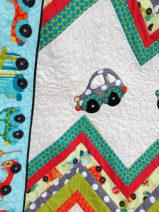 I chose to use a long arm quilting machine to do the free motion quilting on the main parts of the quilt.  However, I wanted the applique' and the chevron to stand out, so I used my domestic machine to carefully outline each car and to stitch in the ditch in the chevrons.  It made for a nice contrast in stitching and gave the quilt depth.