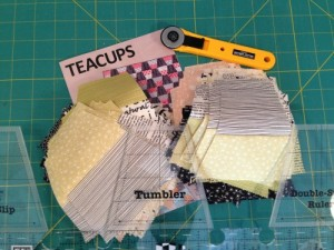 "I am absolutely in love with Creative Grids rulers, especially these specialty rulers.  This pattern, ""Teacups"" by Jay Bird Quilts, uses 2 1/2"" strips to create a tumbler quilt.  Julie from Jay Bird uses the Double-Strip Tumbler ruler in her pattern to cut the tumbler pieces, and I have to say, I really enjoyed using this technique.  (The pattern also includes a template if you don't want to use the ruler.)  If you don't already have 2 1/2"" strips to work with, one side of the ruler is a 2 1/2"" ruler, while the other side of the ruler cuts the tumblers."