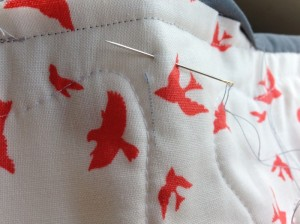 Here's an interesting problem that comes up from time to time- especially on white or black fabrics.  When the fabric is being manufactured, occasionally a stray thread from a previous run flies around the room and ends up getting woven into the new run.  It's not a flaw- it's just something that happens.  Kind of like finding a little piece of stem in a can of green beans.  Anyway, this little blue guy doesn't belong, so I just carefully pick it out using the same needle I am sewing the binding on with.