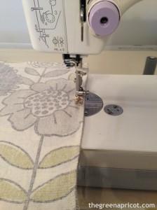 Run a straight stitch along the inside of the serger stitch