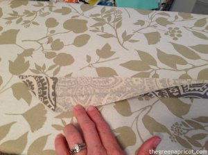 With the raw edges at the top, open the left end of the strip just enough to fold one corner up and press